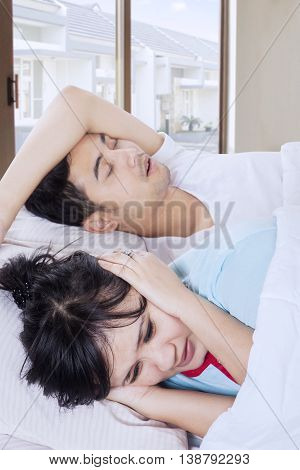 Angry woman can not sleep and covering the ears with hands after listening husband snoring