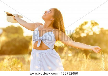 Close up portrait of sensual young woman with open arms and eyes closed in farmland at sunset.