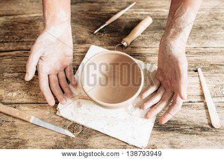 Craftsman hands with pottery and tools on wood close-up. Newcomer at potter studio, workplace of sculptor