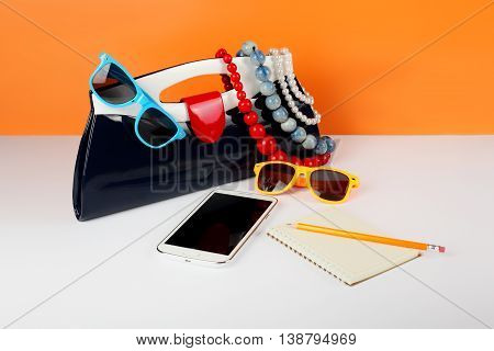 Women's Fashion Accessories. Your style - sunglasses, handbag phone and notebook are decorated with a beads and a pearl necklace.