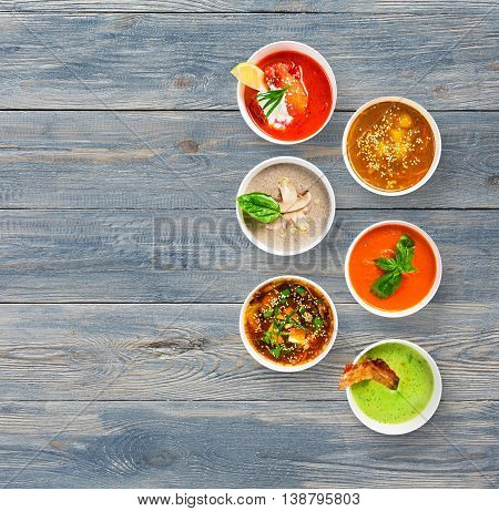 Variety of restaurant hot dishes, healthy food. Japanese miso, asian fish soup, russian borscht, english pea soup with bacon, mushroom soup, spanish gazpacho at blue wood, top view with copy space