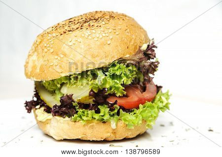 Vegetarian burger. Bun with sesame seeds lettuce slices of tomato and cucumber sauce.