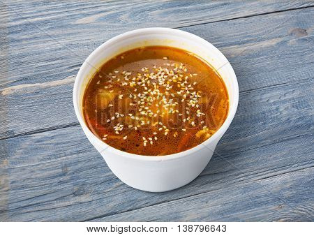 Asian japanese cuisine - red fish soup with sesame closeup at blue wood background, diet and vegetarian food
