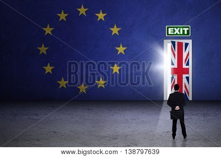 Brexit concept. Young businessman looking at exit door with national flag of England and EU