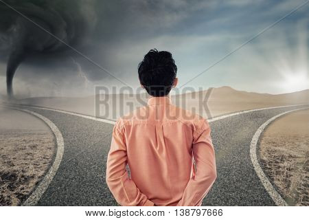 Back view of a young businessman looking at two different road with storm and bright sunlight