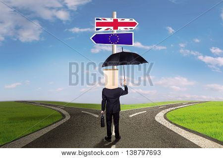 Brexit concept. Businessperson standing on the road and looking at signpost with flag of European Union and Great Britain