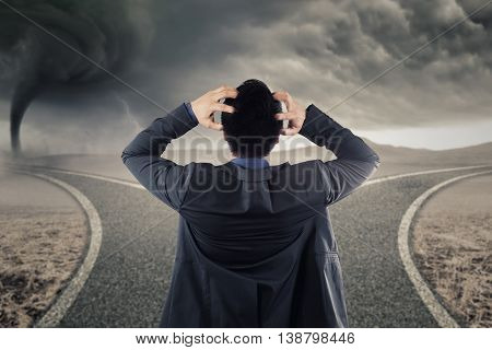 Back view of stressful businessman looking at two road with bright sunlight and storm