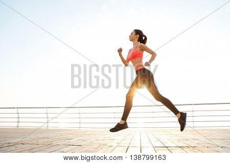 Full length of beautiful slim young sportswoman running on pier at sunrise