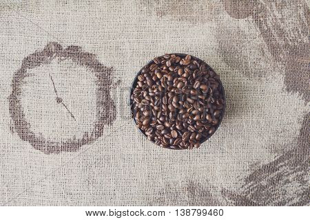 Burlap texture with coffee crop in a bowl background, plenty of robusta beans in plate with clock shape spot near. Sack cloth canvas with copy space. Heap of seeds at hessian textile