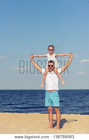 Handsome young dad and his cute little daughter are looking at camera and smiling standing on the beach. Girl is sitting on her father's shoulders