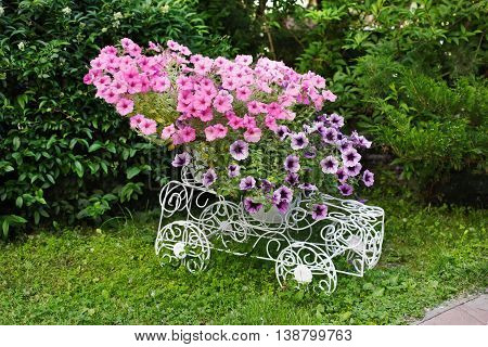 Flowerbed from forged openwork white metal with bright pink flowers. Decorative ironwork car with petunias. Modern garden decoration.