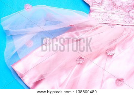 Clothes For Baby Girl On Light Blue Background. Copy Space For Text