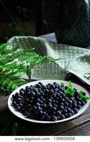 Plate With Bilberry On Wooden Table