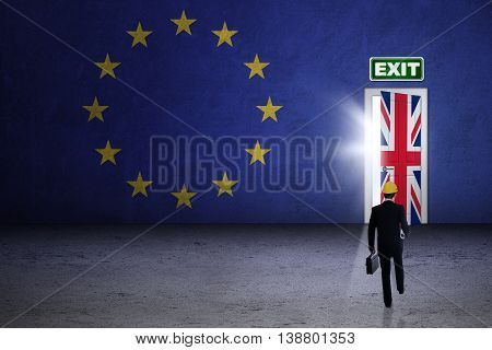 Brexit concept. Male engineer walking toward brexit door with national flag of UK and EU