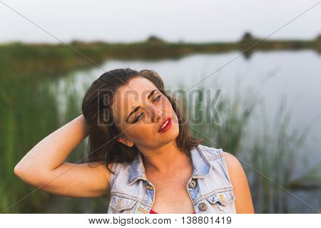 Portrait of redhead girl with blue eyes on nature background. Face of young woman with freckles closeup. Sunset in field