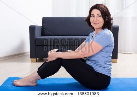 Slim Sporty Mature Woman Doing Exercises On Yoga Mat At Home