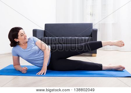 Slim Sporty Mature Woman Doing Stretching Exercises On Yoga Mat At Home