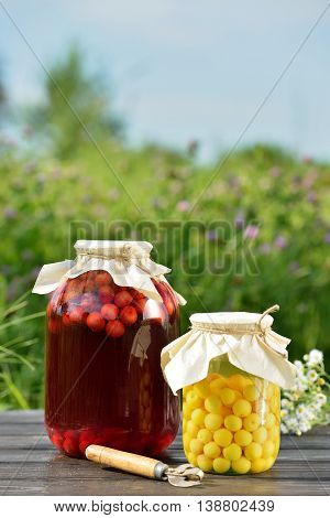 Preserved fruit, sour cherries compote. Canned fruit on wooden table