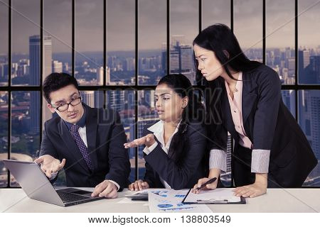 Group of three multiracial entrepreneurs discussing with laptop in the office