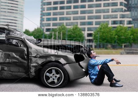 Tired young man waiting a help and sitting in front of a broken car after traffic accident on the road