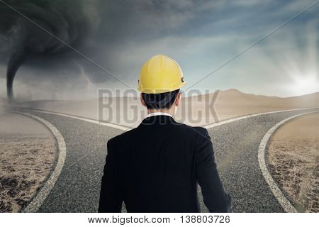 Businessman standing on the road while wearing helmet and looking at two roads with storm and sunlight