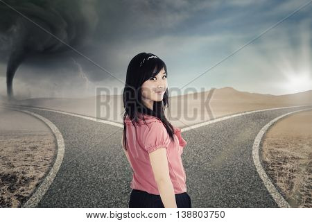 Beautiful young businesswoman standing on the road with two destinations