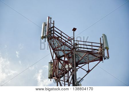 Base transceiver station (BTS) with antenna isolated on blue sky background. Telecommunications radio tower cells