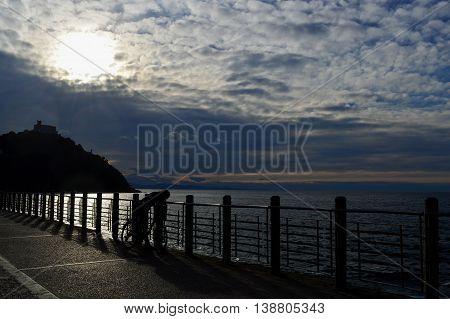 Persona asomándose a ver el mar desde el paseo.