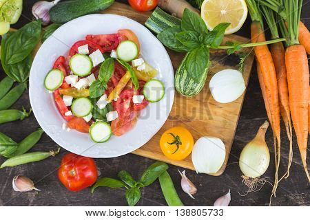Closeup of fresh locally grown organic chopped vegetables on a cutting board on a wooden background. Vegan tomato, basil and cheese recipe. Flat lay top view.