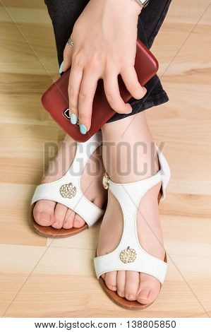 Female hand with a smartphone on the feet in sandals, closeup