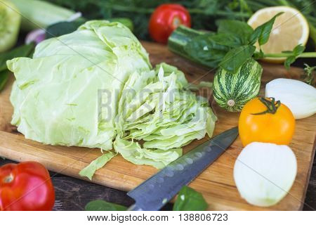 Closeup of fresh locally grown organic chopped vegetables on a cutting board on a wooden background. Vegan recipe.