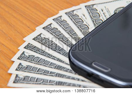 Close up on dollar bills, Smartphone lying on the United States dollars,