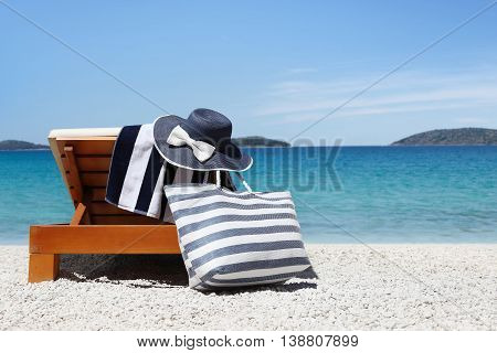 sunbed with bag blue hat and towel on the beach