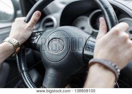 Man drives a car. Hands on the steering wheel.