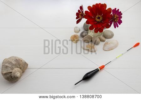 Shell with flowers on white wooden background. Sea fishing.