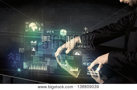 Businessman touching interactive modern desk with technology icons on table