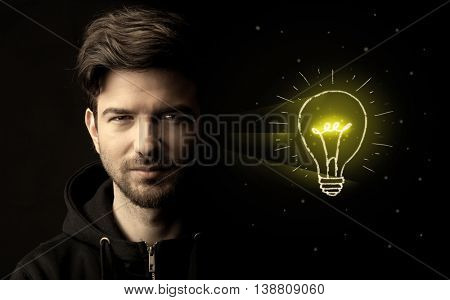 Close-up of young confident man with drawn light bulb