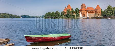 TRAKAI, LITHUANIA - JUNE 22, 2013: Panorama of Trakai castle and a red and green boat in lake Galve in Lithuania