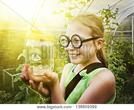 Little girl holds the container with the caught butterfly