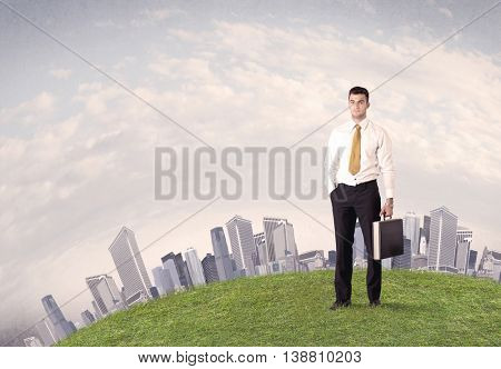 A successful male good looking business man standing in small green grass in front of city landscape with skyscrapers concept.
