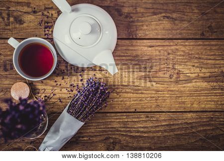 Bunch of dry cut lavender, cup of tea and teapot on wooden table, top view. With spase for product or sign text.