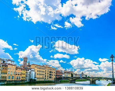 Sunny spring day in Florence, view at Arno river, waterfront cityscape.