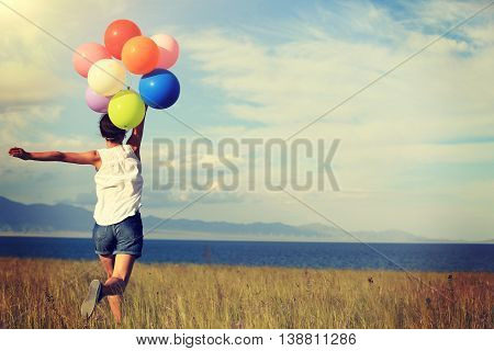 cheering young asian woman running on grassland with colored balloons