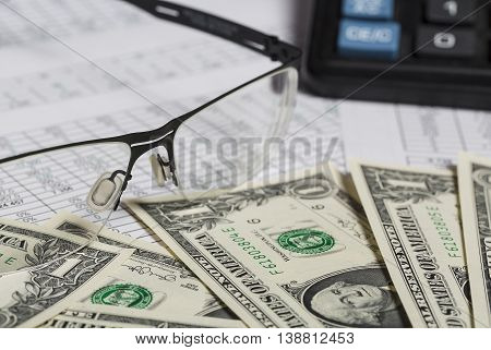 Business research. Closeup of spectacles, dollar bills, calculator on paper with digits.