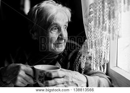 Elderly woman drinking tea looking out the window. Black-and-white photo of high contrast.