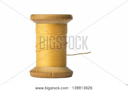 Yellow thread spool close up isolated on white background