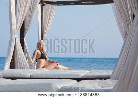 girl resting on the beach in the gazebo