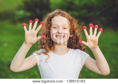 Cute girl with raspberries on her fingers showing her teeth.