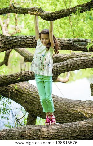 Little Girl on tree trunk on the background of summer park