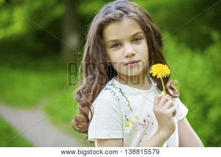 Little girl smelling a yellow dandelion in spring park
